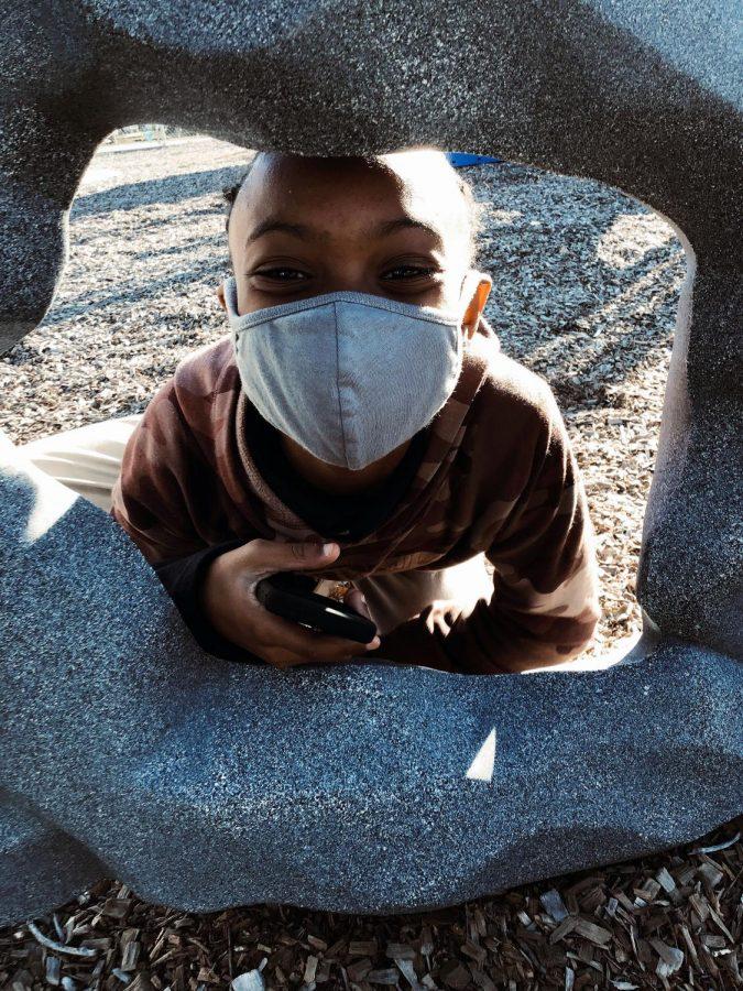 Fourth grader, Ma'kiyah Stone, practices mask safety while playing.