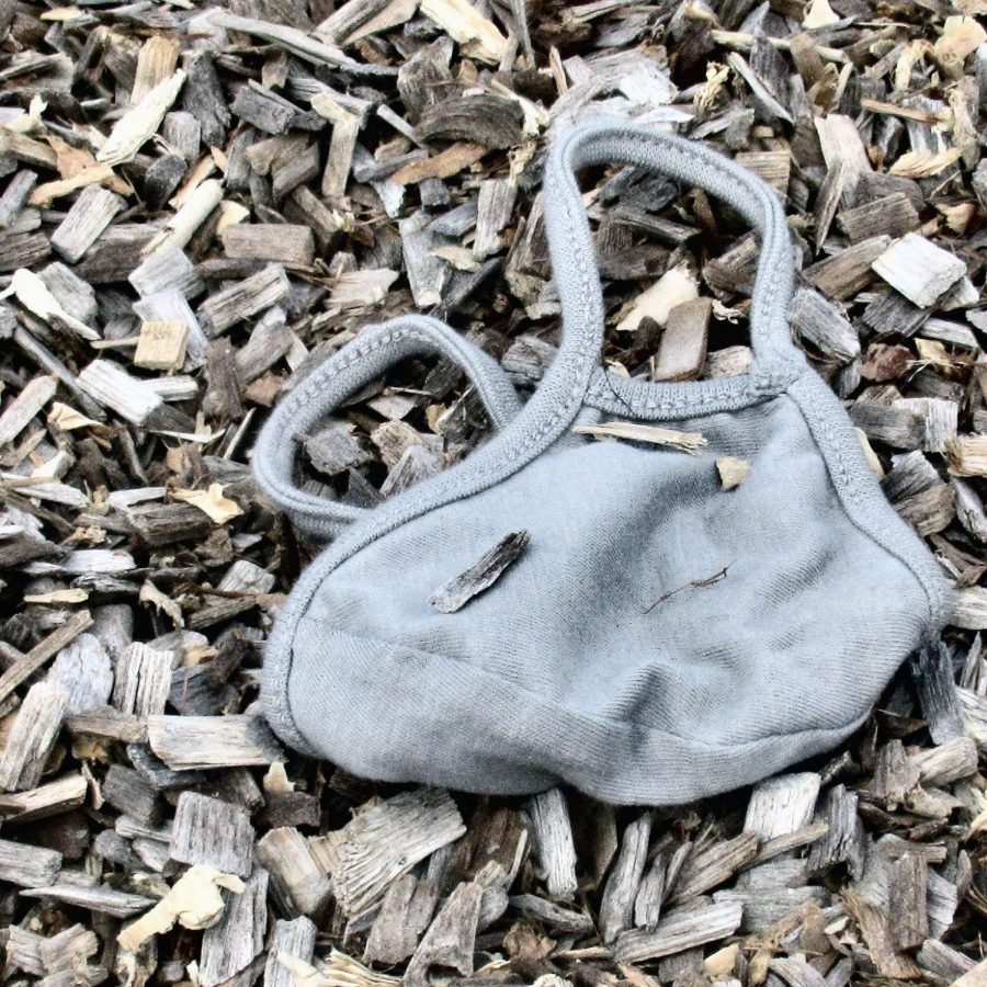A discarded mask lies in the mulch. Masks are required for scholars to attend brick and mortar school.