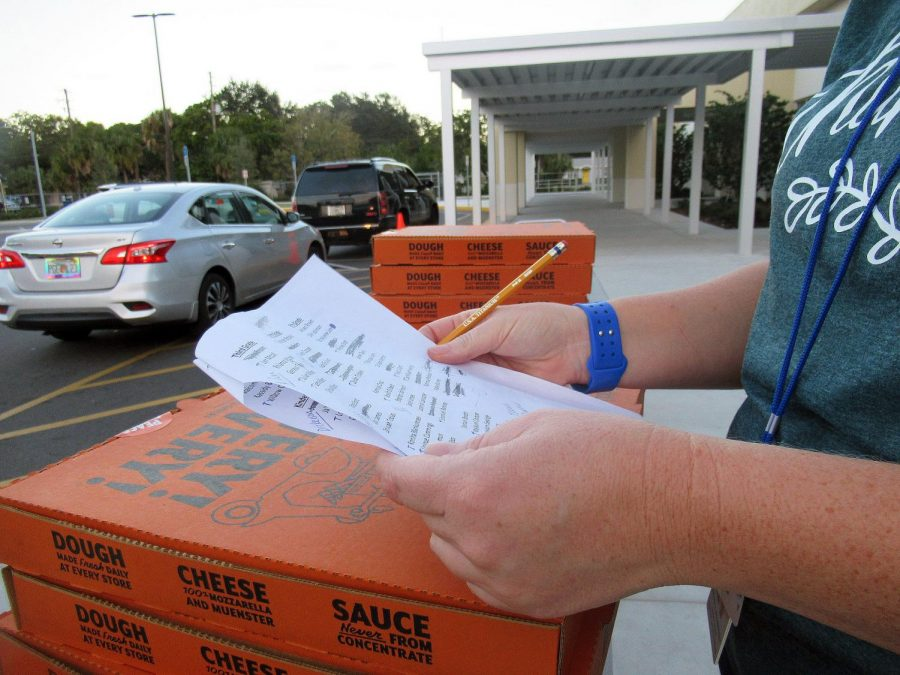 Literacy coach Brooke Johannessen checks off the names of scholars that received free pizza as part of a literacy week.
